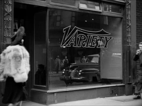 open newsstand on sidewalk male buying 'variety' cars moving bg hotel astor across street. 'variety' on building window women walking sidewalk fg.... - 1943 stock videos & royalty-free footage