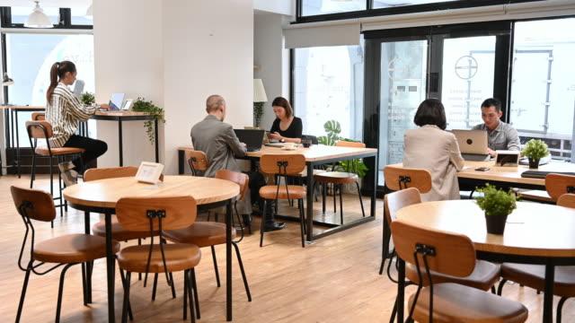 vidéos et rushes de espace de coworking à plan ouvert et gens d'affaires utilisant des ordinateurs portables - hot desking