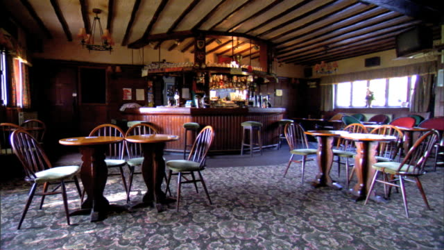 ws open room public house w/ open beam ceiling cocktail tables chairs on patterned carpet bar bg reverse pan to bright bay window seating pan room no... - bay window stock videos & royalty-free footage