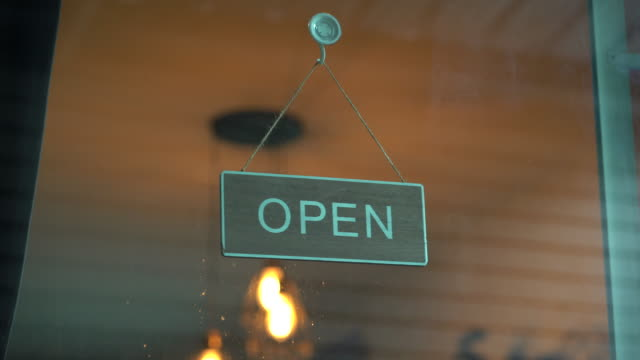 open sign board hanging on glass door of coffee shop - shop sign stock videos & royalty-free footage