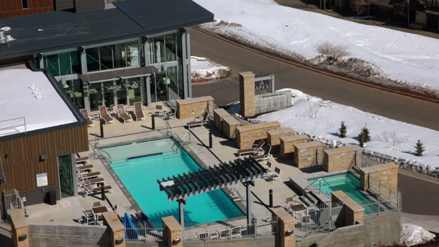 open swimming pool in resort on sunny day over snowy landscape at sunny day - park city, utah - park city stock videos & royalty-free footage