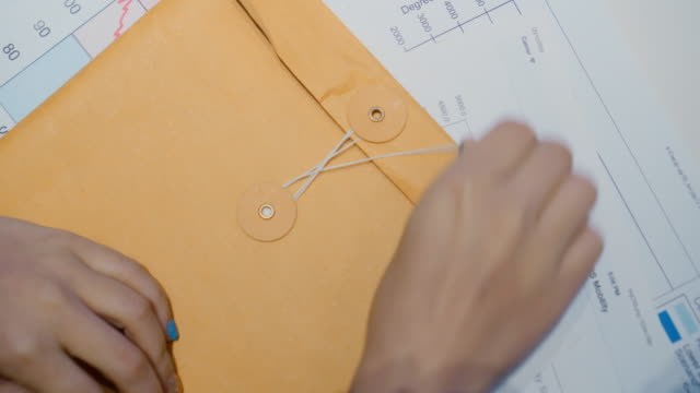 vídeos de stock, filmes e b-roll de abra o envelope do documento, vista superior - conta artigo de armarinho
