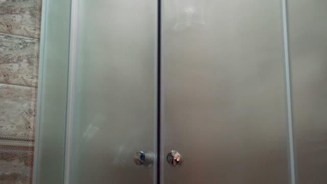 open the shower cabin glass doors before taking a shower, neat and shiny bathroom in a hotel room. - tidy room stock videos & royalty-free footage