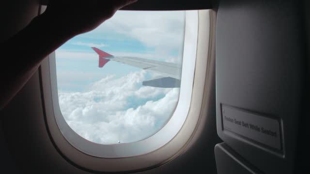 vídeos de stock e filmes b-roll de open the window on airplane through see the sky and clouds - ponto de vista de avião