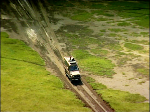 Open topped 4x4 vehicle travels along muddy track Lake Nakuru Kenya