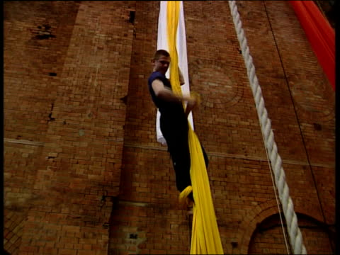 open university offers first ever circus studies bachelors degree; c5f: jon gilbert england: london: int reporter to camera as swings from trapeze... - entertainment occupation stock videos & royalty-free footage