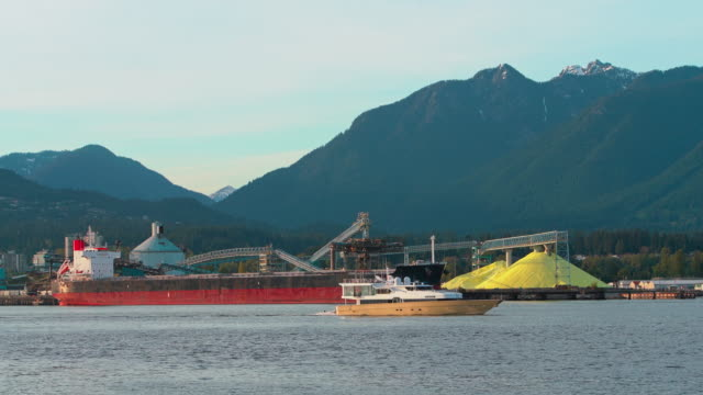 open-air brimstone storage in the industrial district in north vancouver, british columbia. yacht passing through the frame and leaving the scene. - sulphur stock videos & royalty-free footage