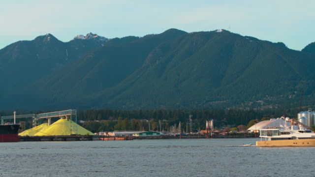 open-air brimstone storage in the industrial district in north vancouver, british columbia. panning camera motion, capturing then following a yacht. - sulphur stock videos & royalty-free footage