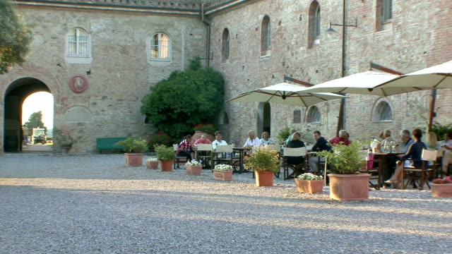 ws pan open-air cafe in castle courtyard / palaia, tuscany, italy - newoutdoors stock videos & royalty-free footage