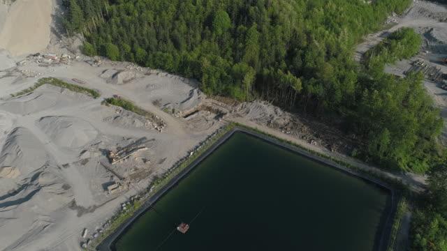 vidéos et rushes de mine opencast et réservoir d'eau technique dans les montagnes voisines gold bar, état de washington. vidéo de drone aérien avec le mouvement de la caméra vers l'avant et l'inclinaison vers le bas. - nord ouest américain