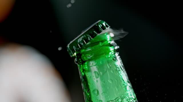 vídeos de stock e filmes b-roll de slo mo opening a bottle of beer - gaseificado