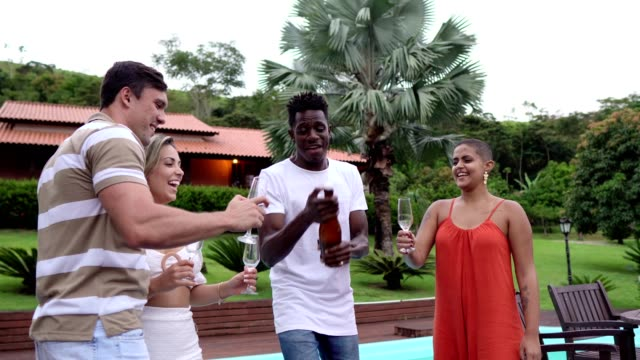 opening a bottle of champagne and toasting with friends - brazilian ethnicity stock videos & royalty-free footage