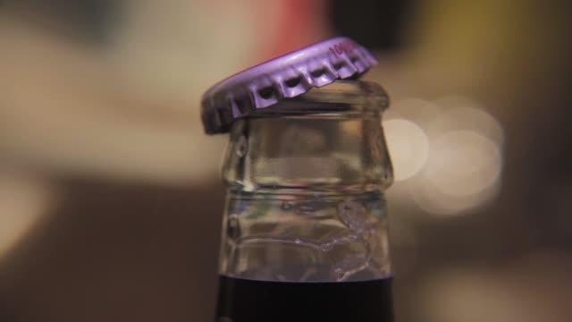 opening a cod beer - ボトルオープナー点の映像素材/bロール