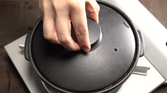 opening a pot-lid of 'mukeunji kimchi-jjim' / south korea - lid stock videos & royalty-free footage