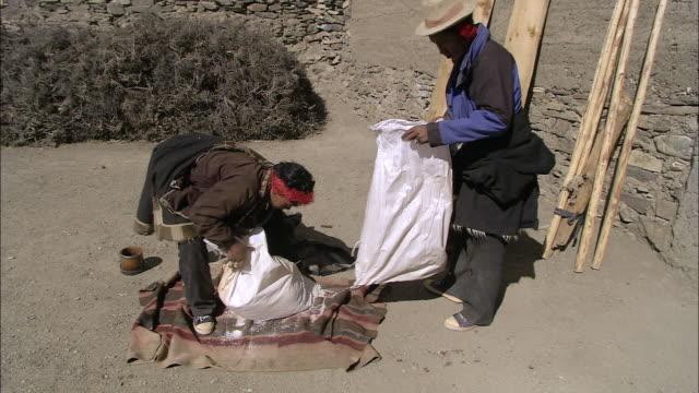 ms opening bag of tibetan salt / saldang village, high himalayas, upper dolpo near tibetan border, nepal - sacca video stock e b–roll