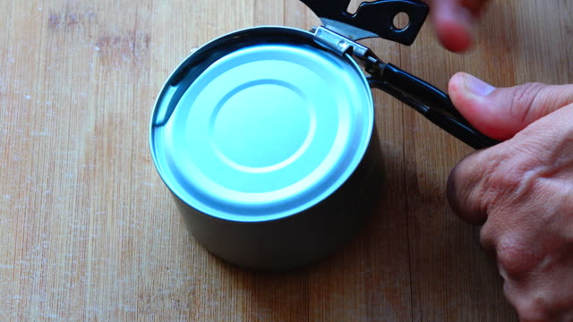 opening canned food with can opener in domestic kitchen - canned food stock videos & royalty-free footage
