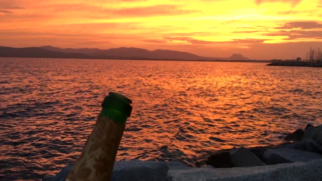 Opening champagne bottle against romantic sunset