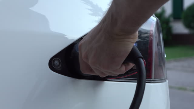 CLOSE UP: Opening charging port and plugging electric cable in, recharging the battery