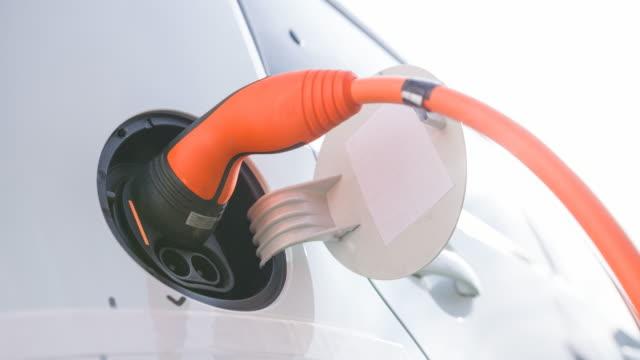 vídeos de stock, filmes e b-roll de abrindo a tampa de porta de carregamento e conectando o cabo de alimentação em carro elétrico - carregamento eletricidade