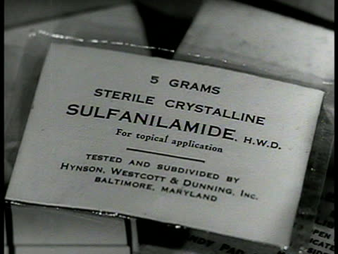 opening first aid kit bag cu label 'sulfanilamide' ms putting bottle of sulfa drugs w/ other assorted sulfa drugs on shelf wwii - hospital corpsman点の映像素材/bロール