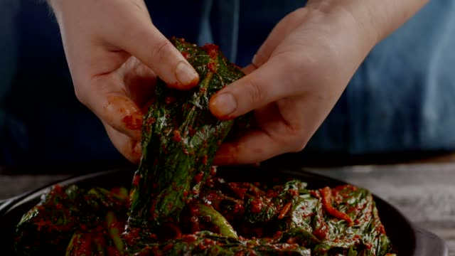 Opening gat (leaf mustard) kimchi (Popular traditional side dish in Korea) with bare hand