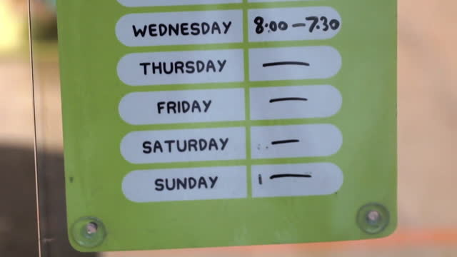 opening hours sign on shop showing they are closed thursday onwards due to coronavirus lockdown - time stock videos & royalty-free footage