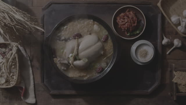 opening lid of nurungji samgyetang (ginseng chicken soup with scorched rice) on the table - burnt stock videos & royalty-free footage