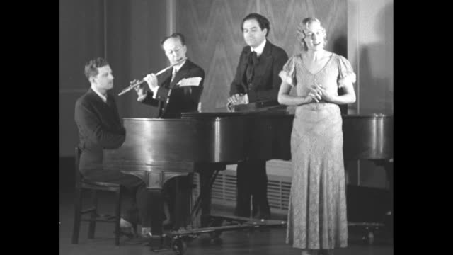 opera singer virginia la rae stands with george marks at a baby grand piano frederico di salle with a flute and opera impresario alfredo salmaggi who... - singer stock videos & royalty-free footage