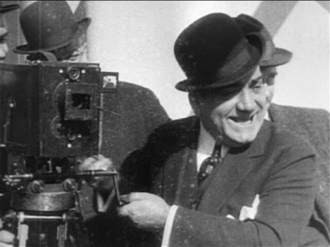 stockvideo's en b-roll-footage met b/w 1909 opera star enrico caruso in bowler hat pretending to crank movie camera / documentary - 1900 1909