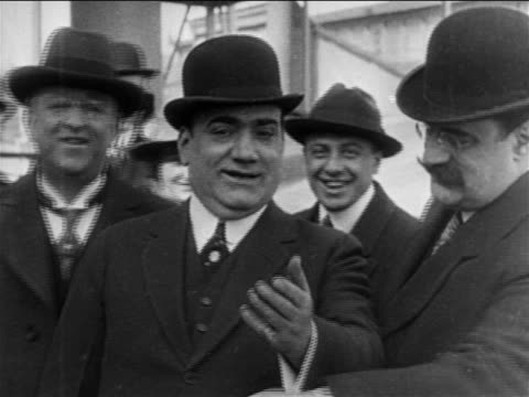stockvideo's en b-roll-footage met b/w 1909 opera star enrico caruso in bowler hat talking to camera smiling / documentary - 1900 1909