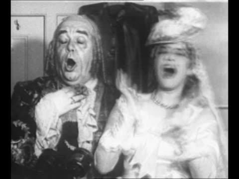 operatic soprano bidu sayao, costumed as character susanna, sings and mugs with operatic bass salvatore baccaloni, in costume as character bartolo,... - ソプラノ点の映像素材/bロール