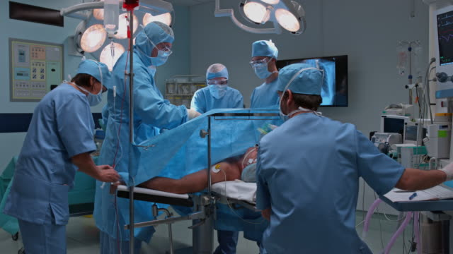 ds operating room with surgical team performing a surgery - operating bildbanksvideor och videomaterial från bakom kulisserna