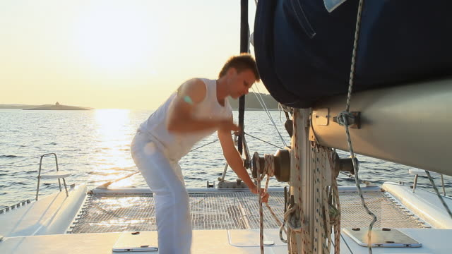hd: operating sail winch while sailing at sunset - sail stock videos and b-roll footage
