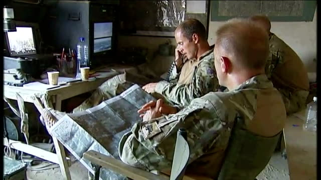 int british officers in base camp set up in mud compound consulting map and communicating with troops using walkie talkie sot - base camp stock videos and b-roll footage