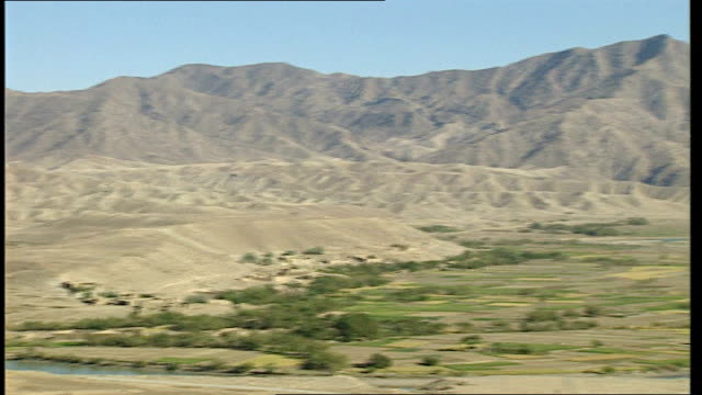 omar khyam evidence tx mountains and river on border between afghanistan and pakistan pan people walking riding bicycles and pulling handcarts along... - crevice stock videos and b-roll footage