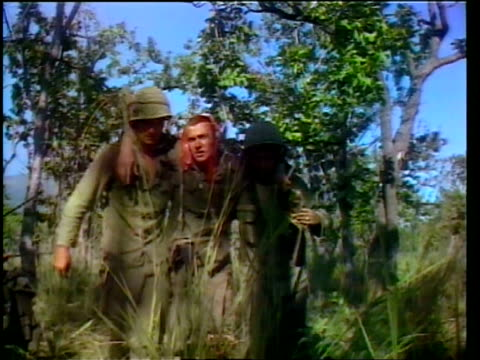 operation long reach, 1st air cavalry division; soldier helping wounded black soldier walk past others sitting on ground in grass / two soldiers... - wounded stock videos & royalty-free footage