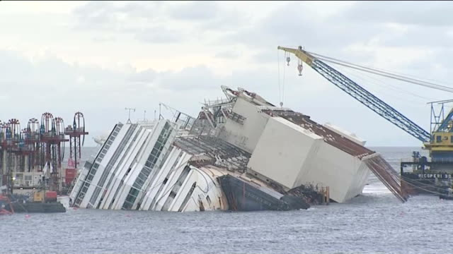 operation to right costa concordia about to begin italy giglio island ext wreck of the cruise ship costa concordia lying on its side with equipment... - giglio video stock e b–roll