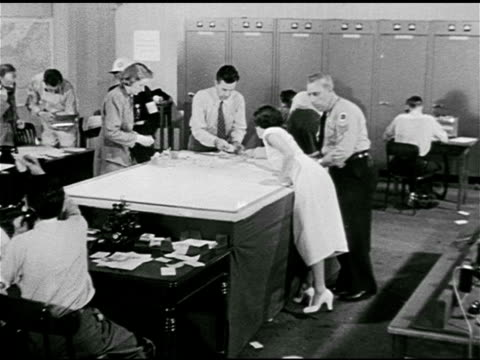 operations center, people busy answering telephones, passing notes, man working on chart, 'debris' push pins in city grid map. 1950s horror, 1950s... - whatif点の映像素材/bロール