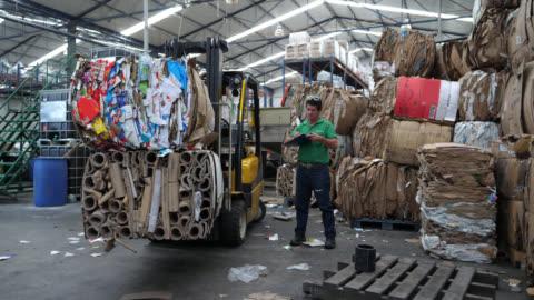stockvideo's en b-roll-footage met operator in een recycling fabriek opschrijven inventaris op het klembord en vervolgens krijgen op de heftruck te verplaatsen van het materiaal - recycling