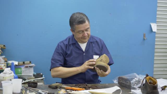 vídeos de stock, filmes e b-roll de fazendo uma qualidade de operador checar um sapato em uma fábrica de sapatos - 1950