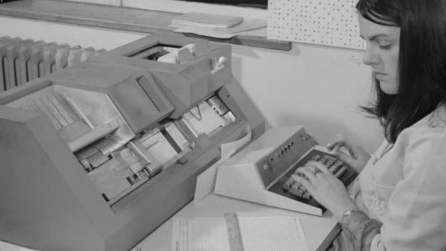 1969 montage operator entering binary program data, keypunch machine processing cards and a compiler machine translating the data into computer language / united kingdom - anno 1969 video stock e b–roll