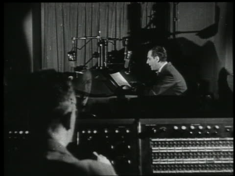stockvideo's en b-roll-footage met b/w 1938 rear view operator in control room watching man with microphone in radio studio - 1938