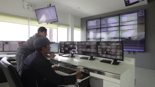 Operator Itipat Kronpho and security personnel Umneuy Kumsandech monitor screens in the control room of the EA Solar Nakornsawan Co solar plant...