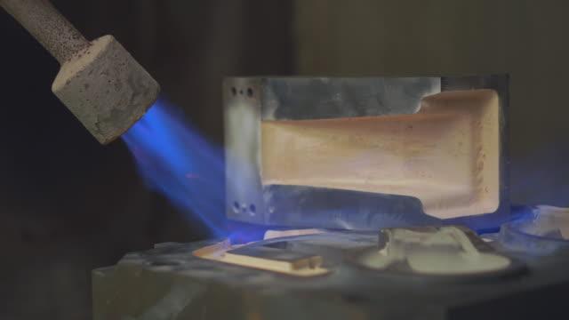 オペレータは生産前に金型を準備し、バーナー炎付きのプレヒート金型、コーティング表面金型、粉砕金型、鋳造工場で一生懸命働く - 緊急用具点の映像素材/bロール