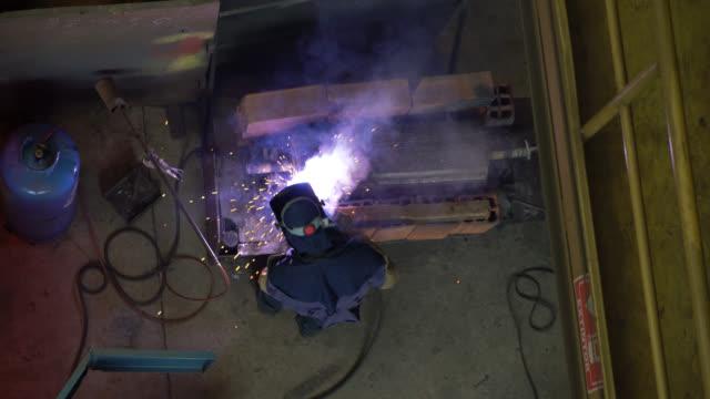 vídeos de stock e filmes b-roll de operator welding on steel at a metallurgy factory - soldador