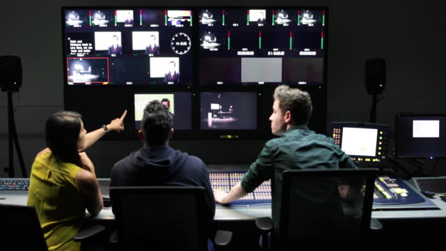 operators in a control room at a television studio - film industry stock-videos und b-roll-filmmaterial