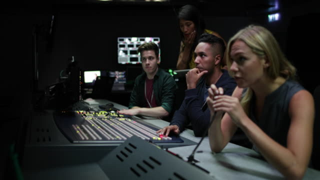 operators in a control room at a television studio - sala di controllo video stock e b–roll
