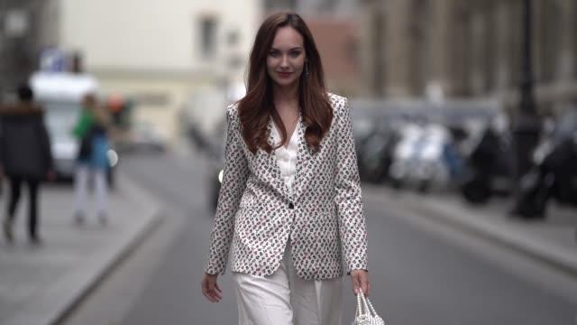 ophelie duvillard wears a floral print blazer jacket, white flared pants, a pearl white bag outside paul & joe, during paris fashion week womenswear... - fashion week stock videos & royalty-free footage