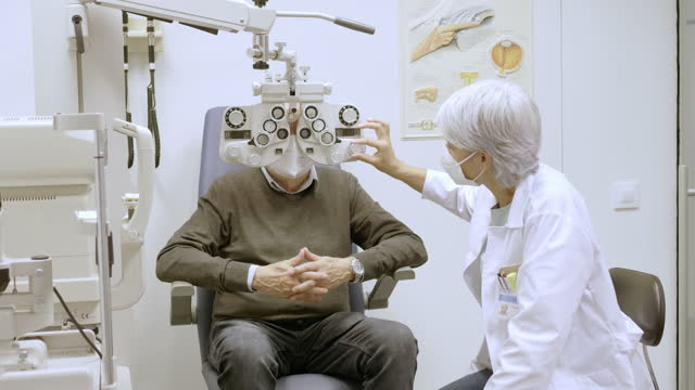 ophthalmologist checking eyesight of male patient - lens optical instrument stock videos & royalty-free footage