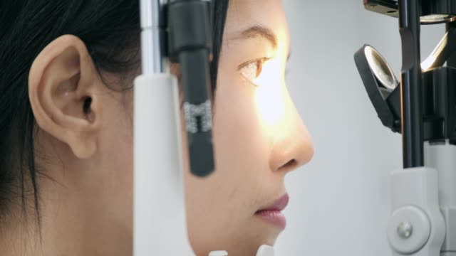 ophthalmologist checks woman's eyes.close up. - ophthalmologist stock videos and b-roll footage